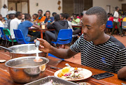 Ruhumuriza Vincent De Paul, who was orphaned by genocide, puts a meal on a plate in the dinning hall at the Agahozo-Shalom Youth Village (ASYV) built to rehabilitate children who lost their families in the 1994 Rwandan genocide, in Eastern Rwanda this week.