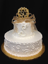 Photo: 2-tier cake featuring Swirl&Dot border on bottom tier w/3-dot clusters on top tier. Scallop top and bottom borders. Fancy gold French ribbon bow & 50th piece toppers.