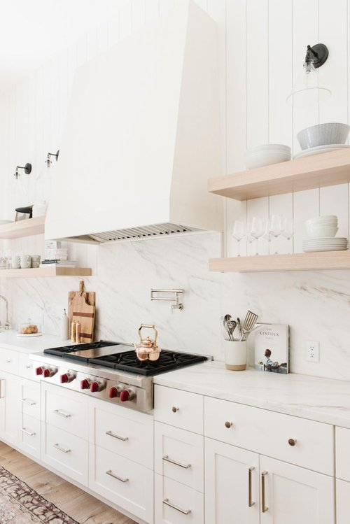 modern farmhouse kitchen with white marble backsplash and white shaker cabinets, brass hardware, white range hood, wooden open shelving