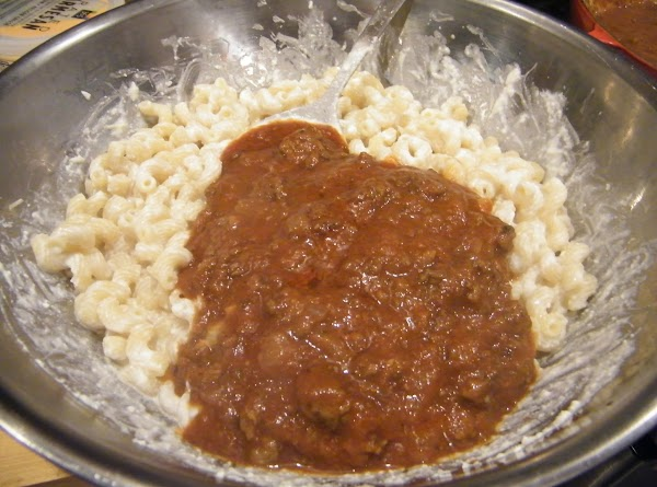 Drain pasta.  Toss hot pasta with cheeses.  Add half the thick meat...