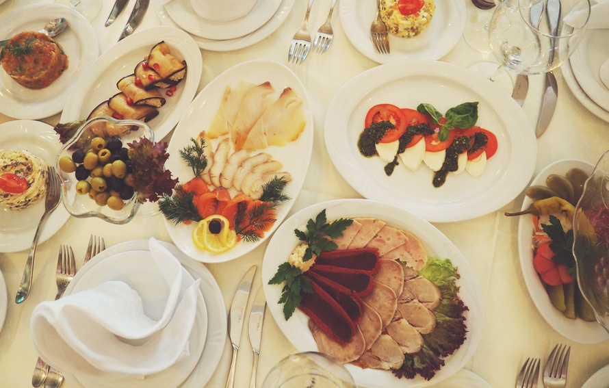 Selection of buffet food laid out on white plates on a table - planning a celebration
