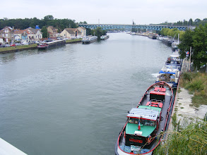 Photo: Here's the view from the bridge upstream along the Oise. There are a number of industrial docks, services and maintenance workshops in this area, which some of these barges are undoubtedly taking advantage of. The Pont Eiffel railway bridge seen here was built in 1892 by the Eiffel company (for metal parts, and Soubigou for masonry), then destroyed in 1944 during WW II by one well placed bomb, and finally rebuilt in 1947.