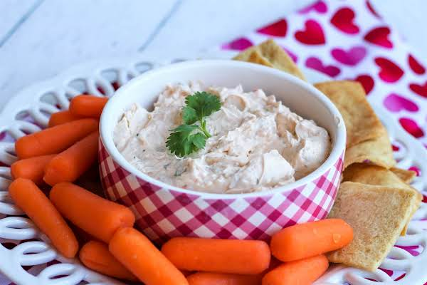 A Bowl Of Love Dip With Crackers And Carrots.