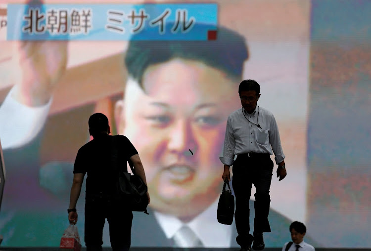 Men walk past a street monitor showing news of North Korea, in Tokyo, Japan. Japan and South Korea joined the US in a military show of force at the weekend. Picture: REUTERS