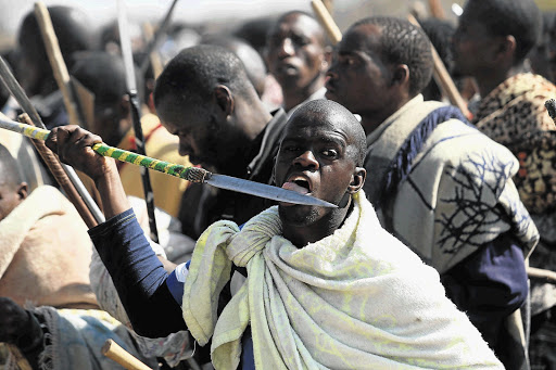 Striking mineworkers brandishing spears and sticks near Lonmin Platinum Mines' Marikana mine at Rustenburg. File photo.