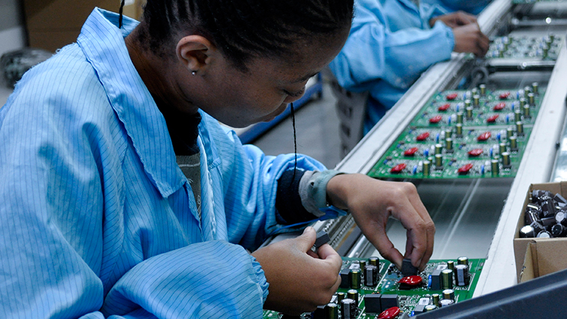 An employee places components on a circuit board.