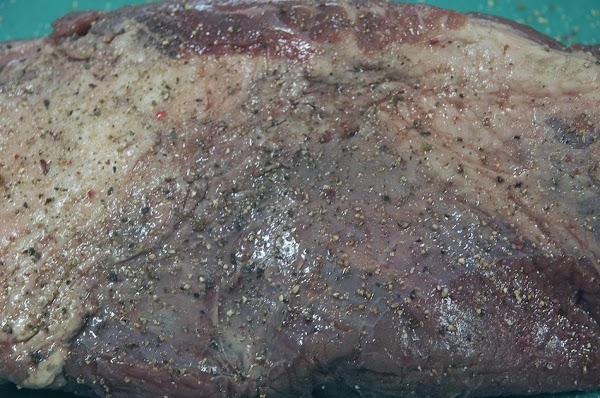 While the onions are browning, season the brisket with a generous amount of kosher...