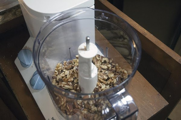 Add the nuts and the salt to a food processor, fitted with an S-Blade.