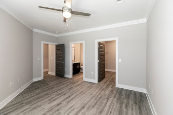 C1L bedroom with wood-inspired flooring and ceiling fan