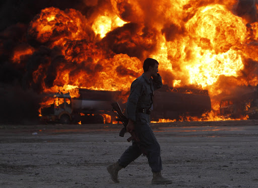 An Afghan policeman runs in front of a tanker on fire in Kabul.