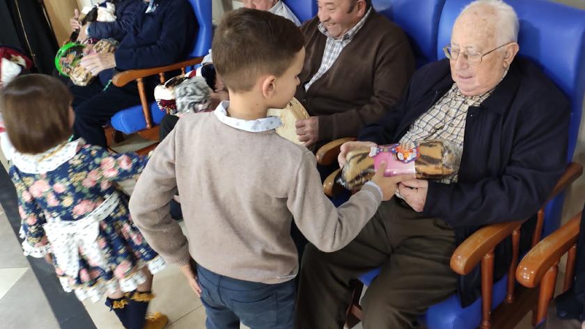 Un niño entrega un regalo a un anciano.