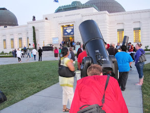 Photo: Guests look through 11-inch telescopes set up on the front grounds, which is a regular activity at the observatory. This one is trained on Saturn.