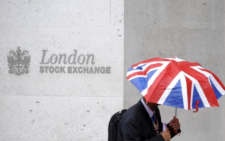 A worker shelters from the rain as he passes the London Stock Exchange in the City of London. Picture: REUTERS/TOBY MELVILLE
