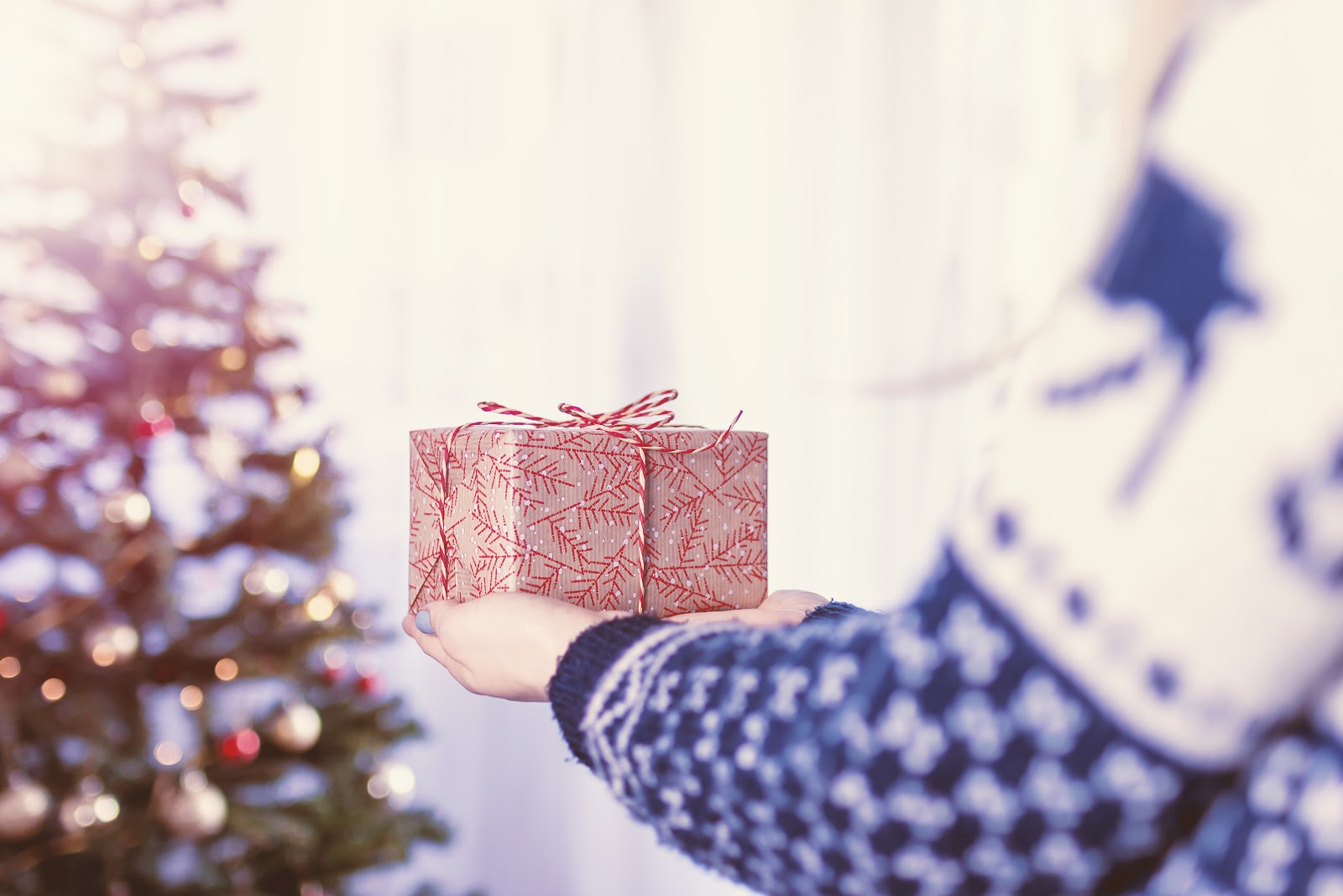 A person carrying a gift in outstretched hands toward a holiday tree.