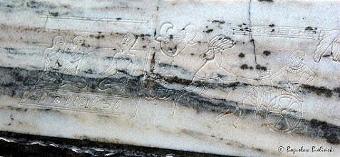 Photo: Podstawę piramidy na grobem Wacława i Agnieszki Januszkiewiczów, pokrywa ostro cięty relief konturowy. Przedstawia on w sposób realistyczny sceny rodzajowe ze starożytnego Egiptu. Umieszczone po lewej stronie reliefu postacie w pozycji siedzącej - zgodnie z manierą stosowaną przez staroegipskich rzeźbiarzy - są dziwnie usztywnione, zapatrzone przed siebie, z głowami w profilu (profil bowiem bez zniekształceń skrótowych oddaje najwierniej zarys podbródka, kształt nosa i ust). Tułów postaci rysowany jest w widoku z przodu, natomiast z profilu rysowane są nogi w sposób aby tylko jedna była widoczna. Przeciwstawieniem statycznej sceny, jest pełen dynamizmu relief po prawej stronie, przedstawiający w pełnym rynsztunku wojownika egipskiego, jadącego na rydwanie zaprzężonym w jednego konia. Kompozycję dopełniają bordiury z pismem hieroglifowym i głową byka.