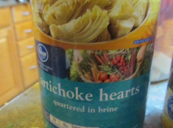 Drain artichokes, and cut into large pieces. Add to salad bowl.