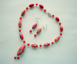 "Photo: PCF- 114, Polymer Clay leaves and flowers cane beads with crystal and glass beads. Base color is red. Flowers are red, orange, purple and white... The beads are: 1 3/4"", 1"", long oval. The necklace is 19.5"" long. Earrings are 2.5"" long. $99.00"