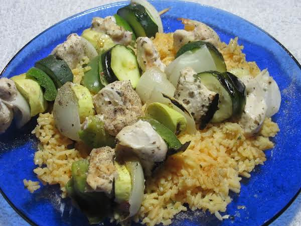 Chunks Of Chicken And Vegetables On A Skewer On A Bed Of Yellow Rice.
