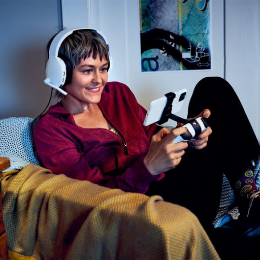 A woman is excited and focused as she plays a game on her phone with the Stadia controller.