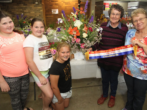 Isabel Graham, Claire Graham and Ebonie Bruce admire Bev McNellee's winning 'Champion Selection of Flowers' entry with Show steward Sue Waugh, right, on Saturday.