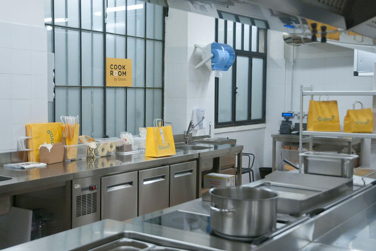 Cook Room allestita da Glovo che predispone una grande cucina condivisibile. Sugli scaffali appaiono buste Glovo gialle con il logo azzurro. Questo è uno spazio di cui diversi ristoratori possono usufruire per organizzare la propria dark kitchen. Fonte: Marketing Ignorante