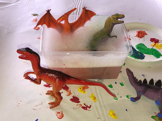 This is a photo of toy dinosaurs in a tub of soapy water.