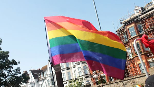 A rainbow Pride flag waves in the wind, carried down a street in a parade.