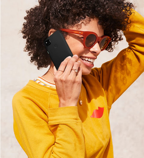 Woman wearing a yellow shirt and sunglasses cheerfully talking on her Just Black Pixel 4a