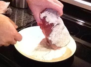 Roll the roast in the seasoned flour, coating all sides.