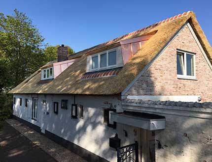 Biały podłużny dom kryty strzechą i oknami dachowymi