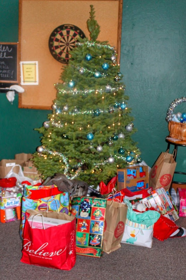 Decorated Christmas tree surrounded by bags of donated items