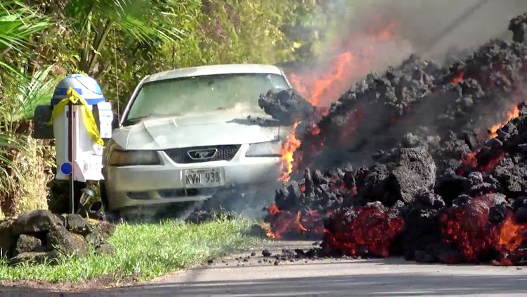 Lava engulfs a Ford Mustang in Puna, Hawaii, on May 6 2018, in this still image obtained from social media video. Picture: WXCHASING VIA REUTERS