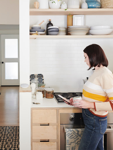 Woman in kitchen, holding coffee mug and Pixel 4. Nest Mini in background on countertop.
