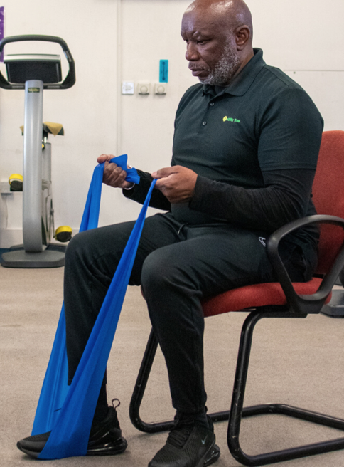 instructor seated in a chair with a resistance band under one foot and stretched in two gripped hands, to perform a bicep curl using the band stretch as resistance