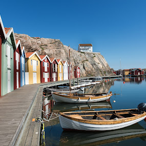 Small boats in a quiet harbor by Mats Andersson - Transportation Boats ( windless, small boat, harbor, evening sun, boats, moored, quiet, dock of the bay, fishing huts )