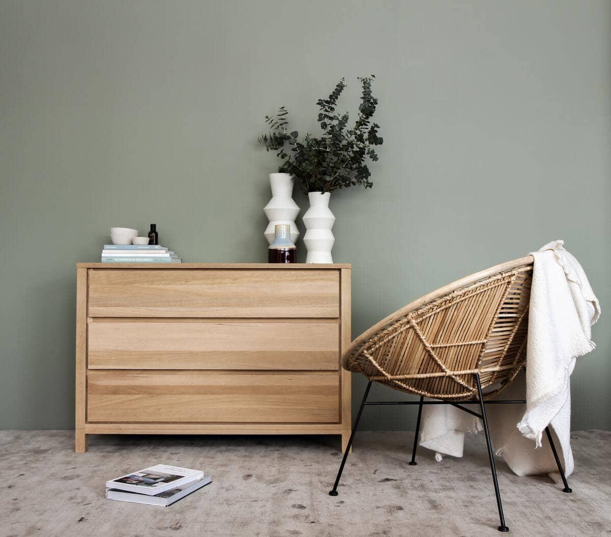 Una cassettiera in legno con dei soprammobili e una sedia in vimini con alcuni vestiti bianchi