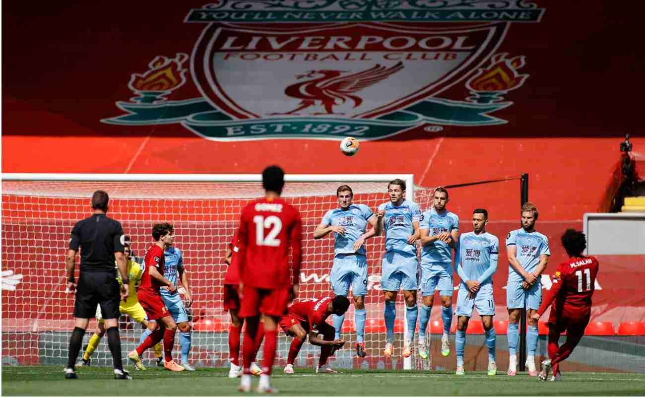 Liverpool's Mo Salah takes a free-kick against Burnley with a huge Liverpool badge in the stadium behind the goals.