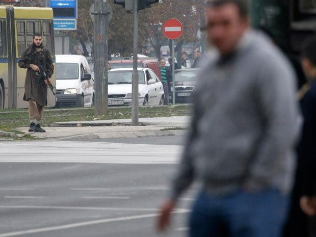 Mevlid Jasarevic (23), stands at an intersection holding an AK-47 (far L), after opening fire upon the United States Embassy in Sarajevo, on October 28, 2011. Jasarevic and two other accomplices have been charged with planning the attacks.