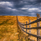 old wooden farme fence in a autumn rural landscape with dark clouds.jpg