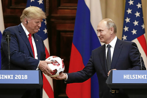 Playing ball: US President Donald Trump receives a football from Russian President Vladimir Putin as they hold a joint news conference after their meeting in Helsinki, Finland, on Monday. Trump offered no criticism of Russia during the briefing. Picture: REUTERS