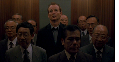 Bill Murray as Bob in Lost in Translation (2003). Bob, a white American, stands in an elevator crowded with Japanese businessmen. Bob visibly stands out as he is a head taller than everyone else.