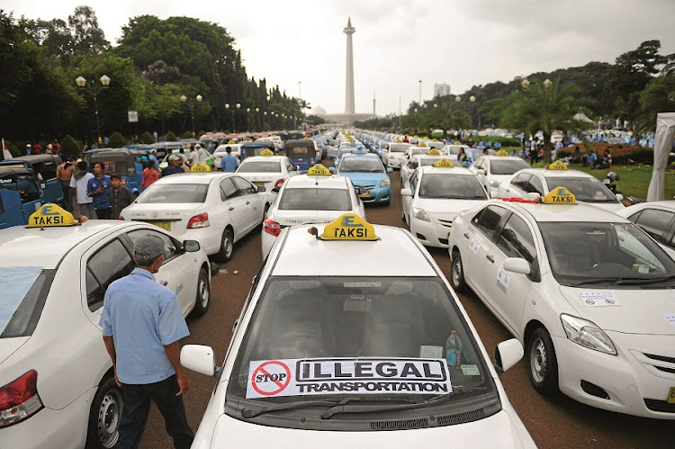 Taxis stand parked in the middle of a road in front of the National Monument during a protest in Jakarta, Indonesia. The drivers, angry over the spread of ride sharing apps like Uber, brought central Jakarta to a standstill. Picture: BLOOMBERG/DIMAS ARDIAN