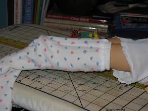 Photo: Turn the socks inside out and put a sock on your doll's leg.  If you want thigh high socks, pull it up to her thigh.  If you want knee highs, pull it up to her knee.    If the sock has a design or a pattern that you want in a specific area, now is the time to line it up.