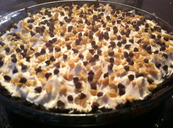 TOP PIE  WITH COOL WHIP MIXTURE N SPRINKLE WITH CHPD PEANUTS N CHOCOLATE...