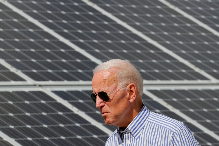 US President Joe Biden walks past solar panels while touring a renewable energy initiative in Plymouth, New Hampshire, the US. Picture: REUTERS/BRIAN SNYDER