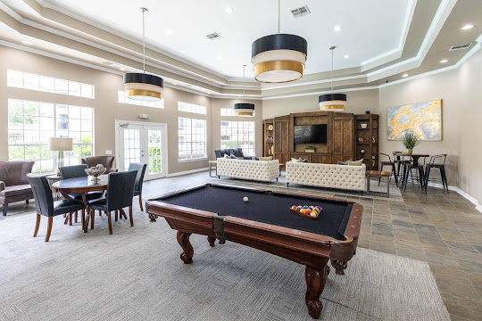Community clubhouse with billiards table, table and chairs, and view of the seating area with a TV