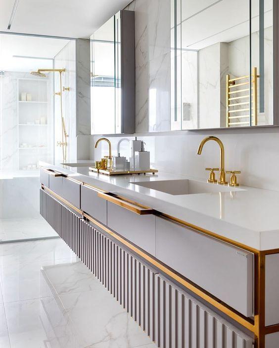 Banheiro com revestimento marmorizado no piso e paredes, bancada branca da pia com detalhes, torneiras e chuveiro dourados e  espelho retangular