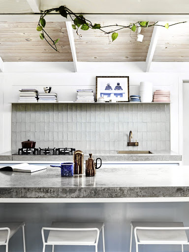 Baby blue cabinets topped with concrete tops made by Damian Oliveri make the heart of the home a show-stopping one.