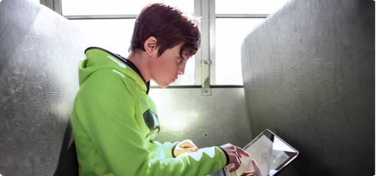 A kid sitting on the bench of a school bus, works on his laptop.