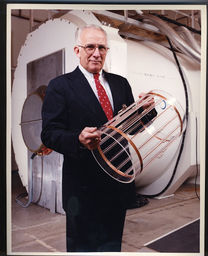 Dr. Walter Robb holding an MRI magnet coil at the GE Research Center